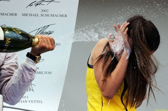 A grid girl being sprayed with champagne to cheer you up.